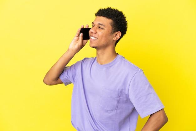 Jonge afro-amerikaanse man geïsoleerd op gele achtergrond die een gesprek voert met de mobiele telefoon