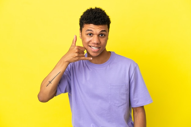 Jonge afro-amerikaanse man geïsoleerd op gele achtergrond telefoon gebaar maken. bel me terug teken