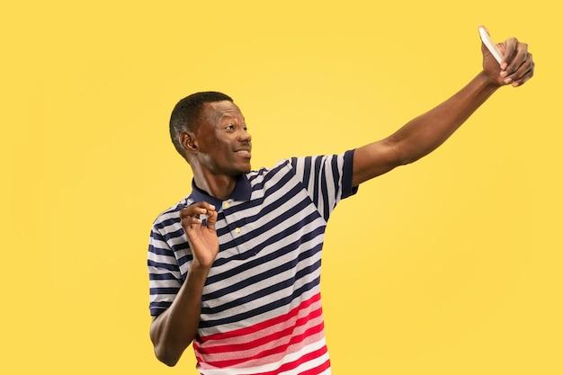 Jonge afro-amerikaanse man geïsoleerd op gele studio, menselijke emoties concept.