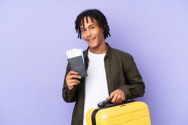 Jonge afro-amerikaanse man geïsoleerd op paarse muur in vakantie met koffer en paspoort