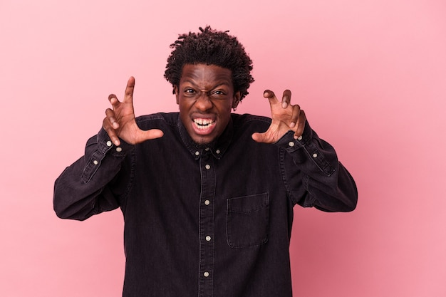 Jonge afro-amerikaanse man geïsoleerd op roze achtergrond boos schreeuwen met gespannen handen.