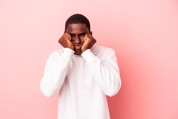 Jonge afro-amerikaanse man geïsoleerd op roze achtergrond huilen, ongelukkig met iets, pijn en verwarring concept.