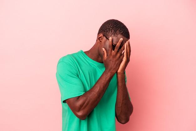 Jonge afro-amerikaanse man geïsoleerd op roze achtergrond knipperen door vingers bang en nerveus.