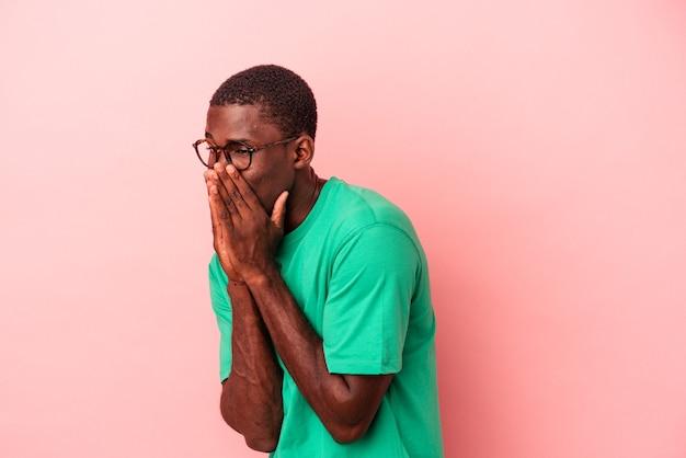 Jonge afro-amerikaanse man geïsoleerd op roze achtergrond lachen om iets, mond bedekken met handen.