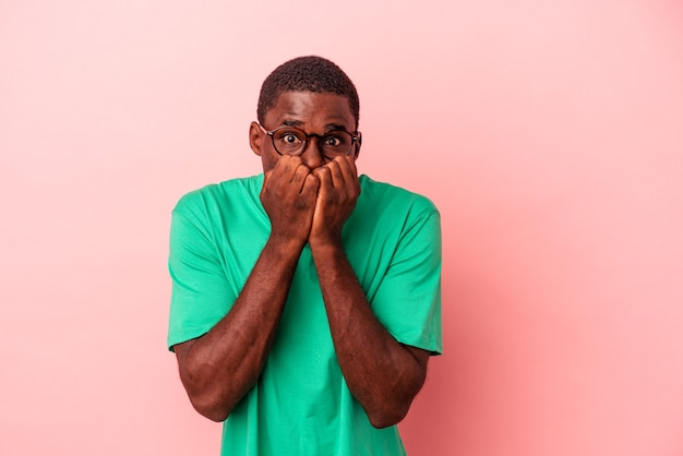 Jonge afro-amerikaanse man geïsoleerd op roze achtergrond vingernagels bijten, nerveus en erg angstig.