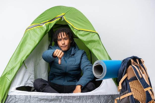 Jonge afro-amerikaanse man in een camping groene tent met duim omlaag met negatieve expressie