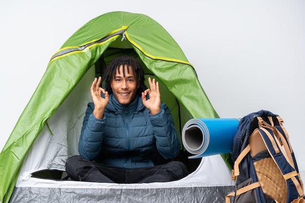 Jonge afro-amerikaanse man in een camping groene tent met een ok teken met vingers