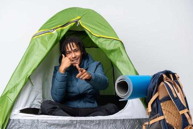 Jonge afro-amerikaanse man in een camping groene tent telefoon gebaar maken en voorzijde wijzen