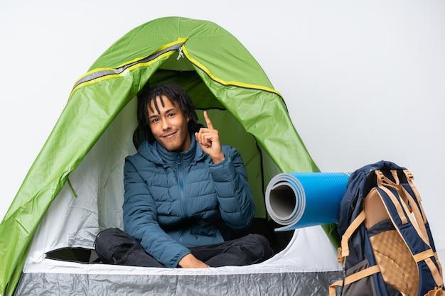 Jonge afro-amerikaanse man in een camping groene tent tonen en opheffen van een vinger in teken van het beste
