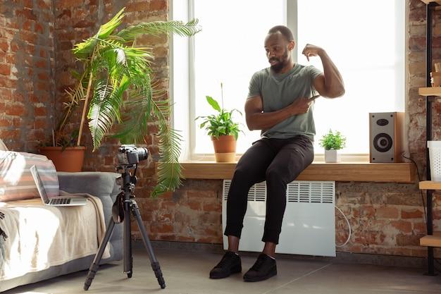 Jonge afro-amerikaanse man lesgeven thuis online cursussen van fitness, aërobe, sportieve levensstijl tijdens quarantaine, opname op camera, streaming
