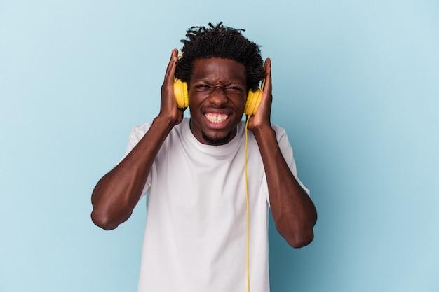 Jonge afro-amerikaanse man luistert naar muziek geïsoleerd op een blauwe achtergrond die oren bedekt met handen.