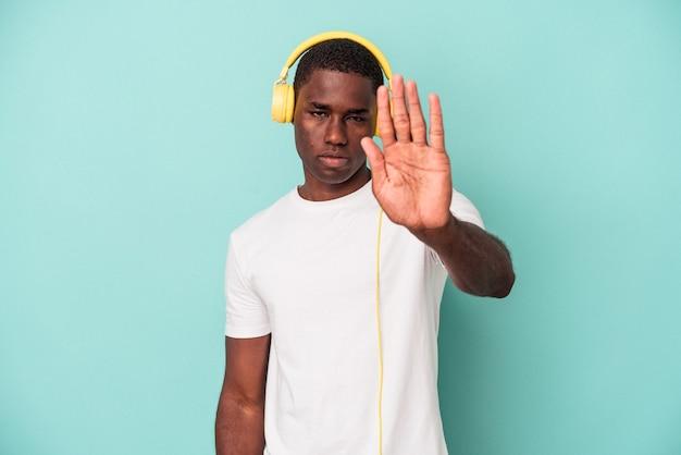 Jonge afro-amerikaanse man luistert naar muziek geïsoleerd op een blauwe achtergrond, staande met uitgestrekte hand die een stopbord toont, waardoor je wordt voorkomen.
