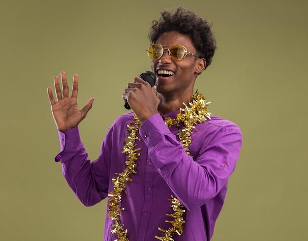 Jonge afro-amerikaanse man met bril met klatergoud guirlande rond de nek met microfoon houden hand in de lucht zingen met gesloten ogen geïsoleerd op olijfgroene achtergrond