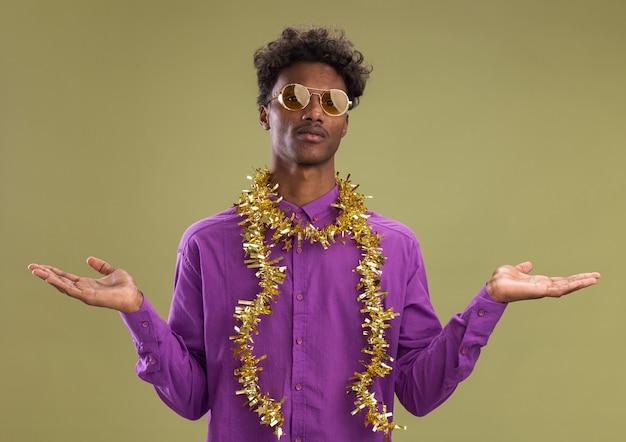 Jonge afro-amerikaanse man met bril met klatergoud slinger om nek met lege handen geïsoleerd op olijfgroene muur