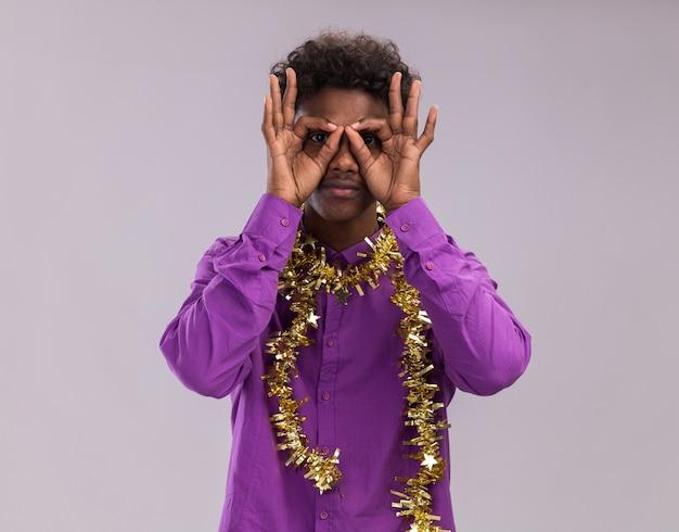 Jonge afro-amerikaanse man met bril met klatergoud slinger rond nek kijken camera doen blik gebaar met handen als verrekijker geïsoleerd op witte achtergrond