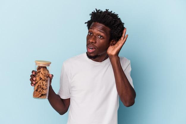 Jonge afro-amerikaanse man met chocoladeschilferkoekjes geïsoleerd op een blauwe achtergrond en probeert een roddel te luisteren.