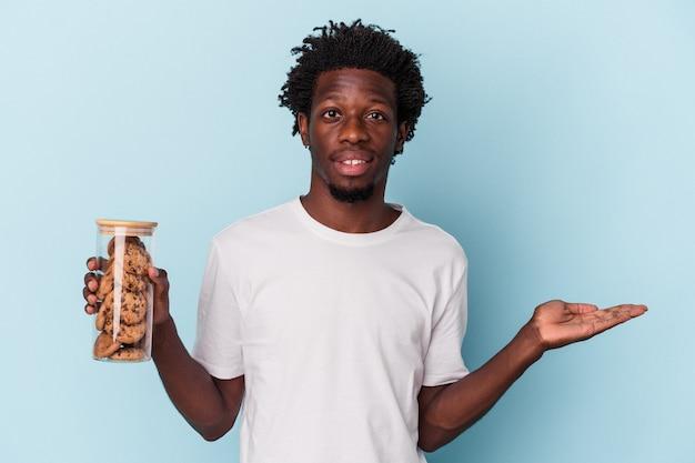 Jonge afro-amerikaanse man met chocoladeschilferkoekjes geïsoleerd op een blauwe achtergrond met een kopieerruimte op een palm en met een andere hand op de taille.