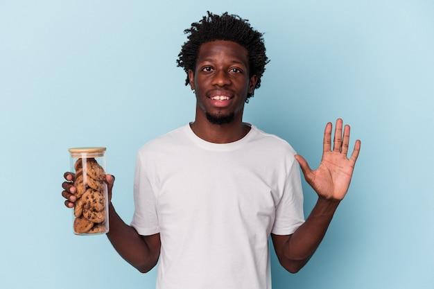 Jonge afro-amerikaanse man met chocoladeschilfers cookies geïsoleerd op blauwe achtergrond glimlachend vrolijk nummer vijf met vingers.