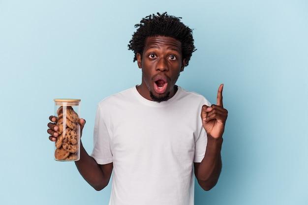 Jonge afro-amerikaanse man met chocoladeschilfers cookies geïsoleerd op blauwe achtergrond met een idee, inspiratie concept.