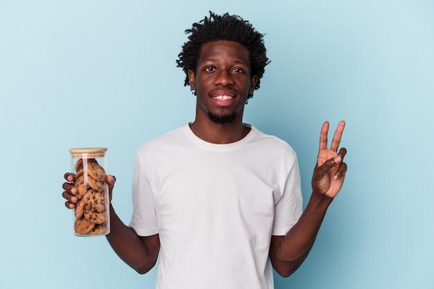 Jonge afro-amerikaanse man met chocoladeschilfers cookies geïsoleerd op blauwe achtergrond met nummer twee met vingers.