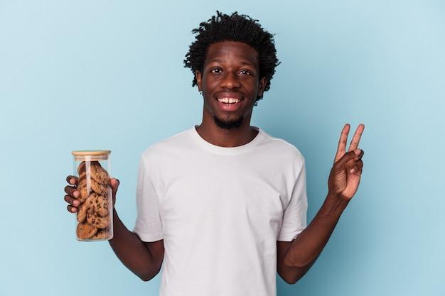 Jonge afro-amerikaanse man met chocoladeschilfers cookies geïsoleerd op blauwe achtergrond vrolijk en zorgeloos met een vredessymbool met vingers.