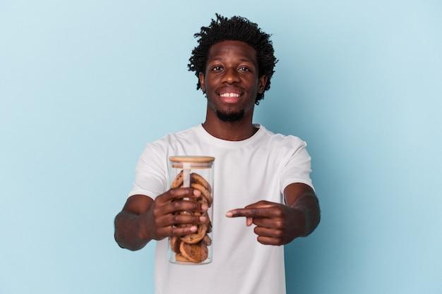 Jonge afro-amerikaanse man met chocoladeschilfers cookies geïsoleerd op blauwe achtergrond
