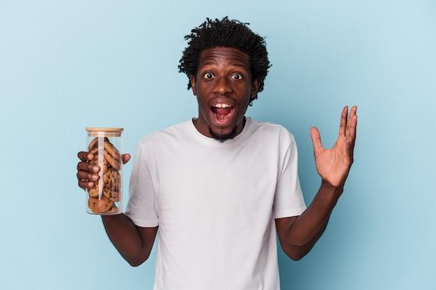 Jonge afro-amerikaanse man met chocoladeschilferskoekjes geïsoleerd op blauwe achtergrond die een aangename verrassing ontvangt, opgewonden en handen opsteken.