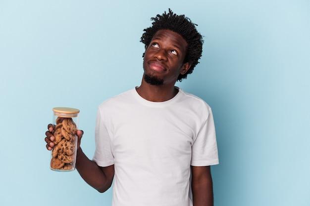 Jonge afro-amerikaanse man met chocoladeschilferskoekjes geïsoleerd op blauwe achtergrond, dromend van het bereiken van doelen en doeleinden