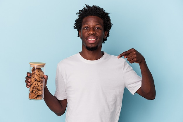 Jonge afro-amerikaanse man met chocoladeschilferskoekjes geïsoleerd op een blauwe achtergrond persoon die met de hand wijst naar de ruimte van een shirtkopie, trots en zelfverzekerd?