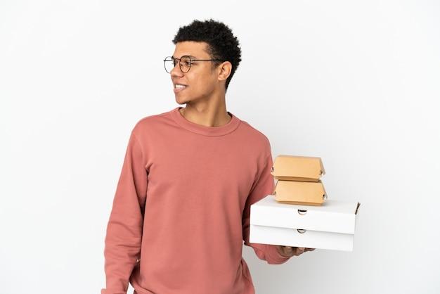 Jonge afro-amerikaanse man met een hamburger en pizza's geïsoleerd op een witte achtergrond die naar de zijkant kijkt en glimlacht