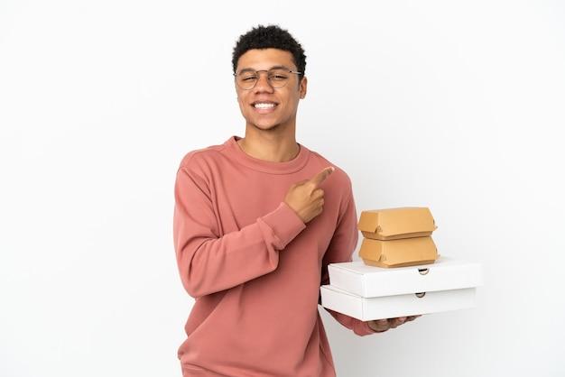 Jonge afro-amerikaanse man met een hamburger en pizza's geïsoleerd op een witte achtergrond die naar de zijkant wijst om een product te presenteren