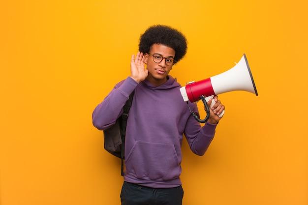 Jonge afro-amerikaanse man met een megafoon probeert een roddel te luisteren