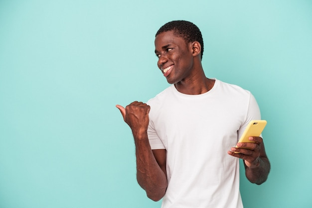 Jonge afro-amerikaanse man met een mobiele telefoon geïsoleerd op blauwe achtergrond wijst met duimvinger weg, lachend en zorgeloos.