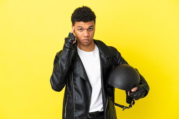 Jonge afro-amerikaanse man met een motorhelm geïsoleerd op gele achtergrond denken een idee