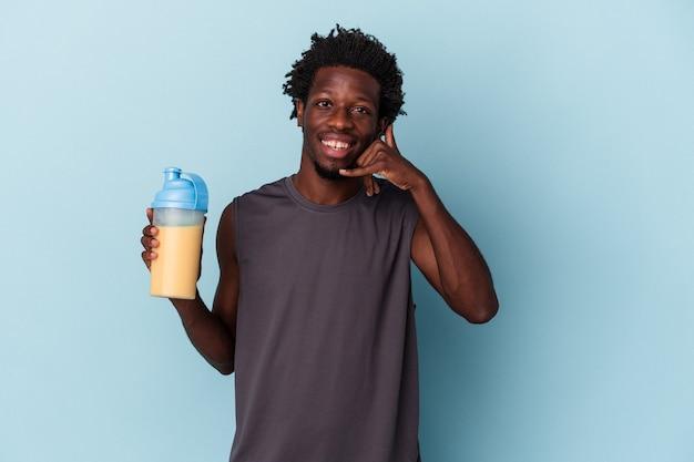 Jonge afro-amerikaanse man met eiwit milkshake geïsoleerd op blauwe achtergrond met een mobiel telefoongesprek gebaar met vingers.