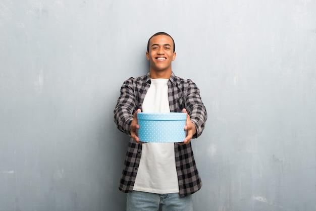 Jonge afro-amerikaanse man met geruite hemd geschenkdozen in handen te houden