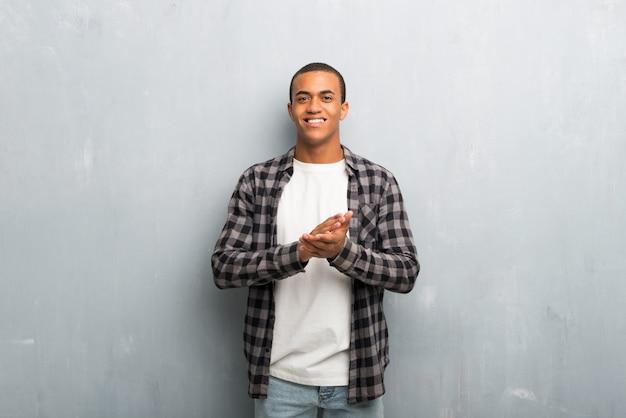 Jonge afro-amerikaanse man met geruite shirt applaudisseren na de presentatie in een conferentie