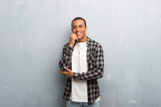 Jonge afro-amerikaanse man met geruite shirt lachend met een zoete uitdrukking