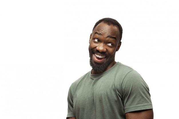 Jonge afro-amerikaanse man met grappige, ongebruikelijke populaire emoties en gebaren geïsoleerd op wit
