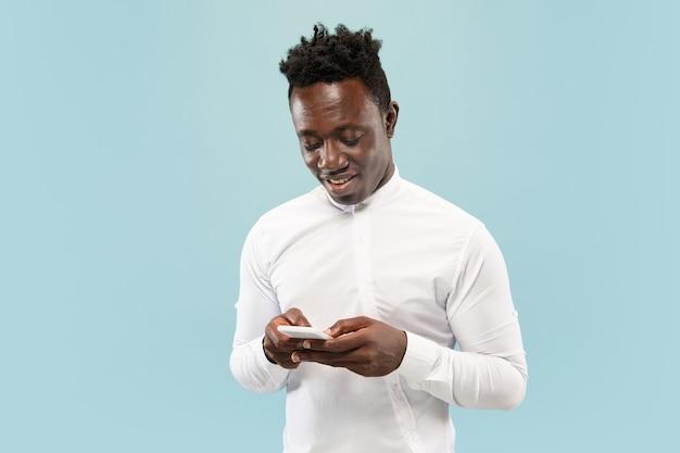 Jonge afro-amerikaanse man met smartphone geïsoleerd op blauwe studio achtergrond