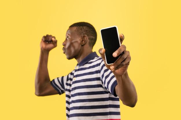Jonge afro-amerikaanse man met smartphone geïsoleerd op gele studio achtergrond, gezichtsuitdrukking. mooi mannelijk halflang portret. concept van menselijke emoties, gezichtsuitdrukking.