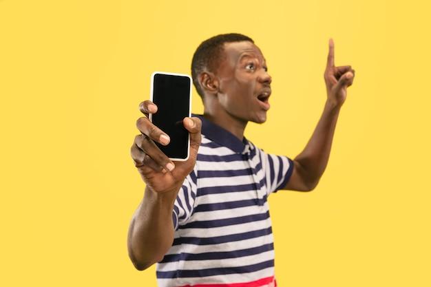 Jonge afro-amerikaanse man met smartphone geïsoleerd op gele studio achtergrond