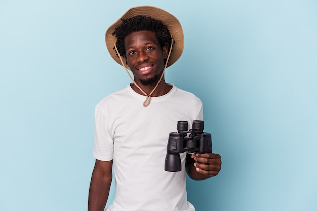 Jonge afro-amerikaanse man met verrekijker geïsoleerd op blauwe achtergrond gelukkig, glimlachend en vrolijk.