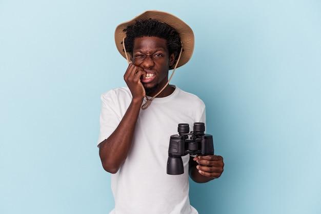 Jonge afro-amerikaanse man met verrekijker geïsoleerd op blauwe achtergrond vingernagels bijten, nerveus en erg angstig.