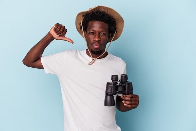 Jonge afro-amerikaanse man met verrekijker geïsoleerd op blauwe achtergrond voelt zich trots en zelfverzekerd, voorbeeld om te volgen.