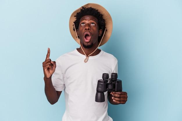 Jonge afro-amerikaanse man met verrekijker geïsoleerd op blauwe achtergrond wijzend ondersteboven met geopende mond.