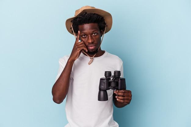 Jonge afro-amerikaanse man met verrekijker geïsoleerd op blauwe achtergrond wijzende tempel met vinger, denken, gericht op een taak.