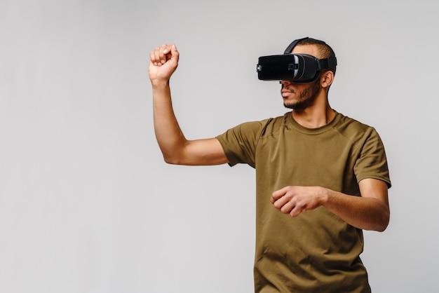 Jonge afro-amerikaanse man met vr virtual reality headset over grijze muur