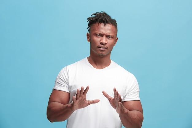 Jonge afro-amerikaanse man met weerzinwekkende uitdrukking iets afstoten, geïsoleerd op het blauw