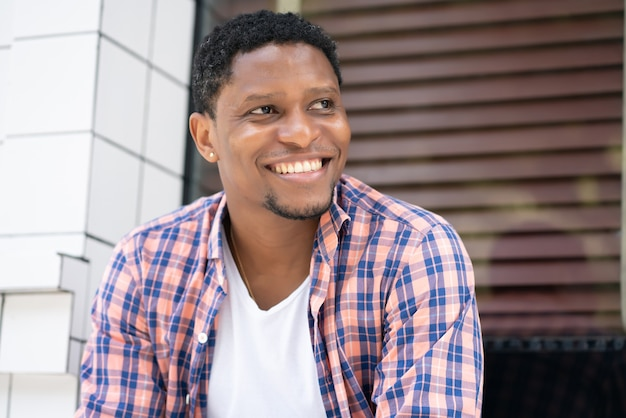 Jonge afro-amerikaanse man ontspannen en genieten zittend bij een etalage op straat.